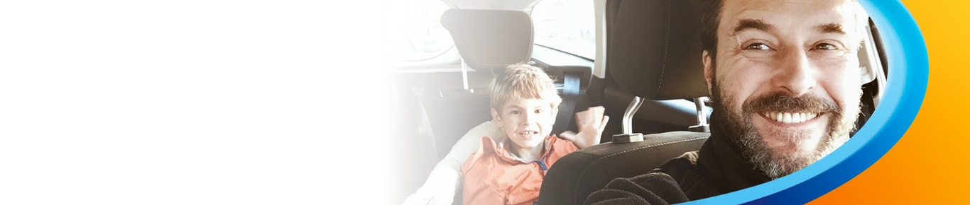 Man driving son in car, smiling